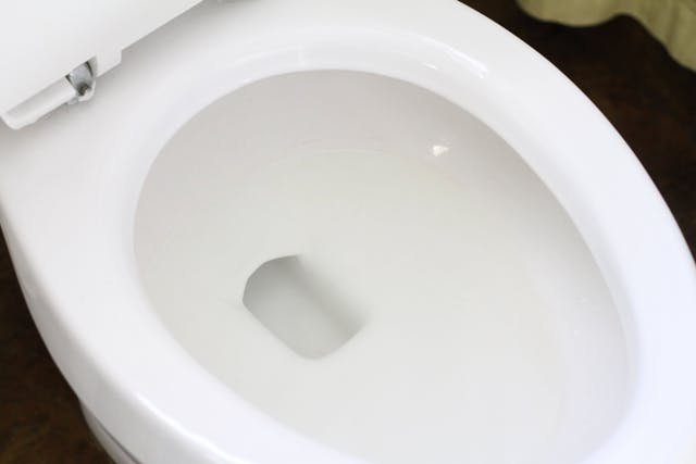 cleaning toilet bowl with vinegar and baking soda